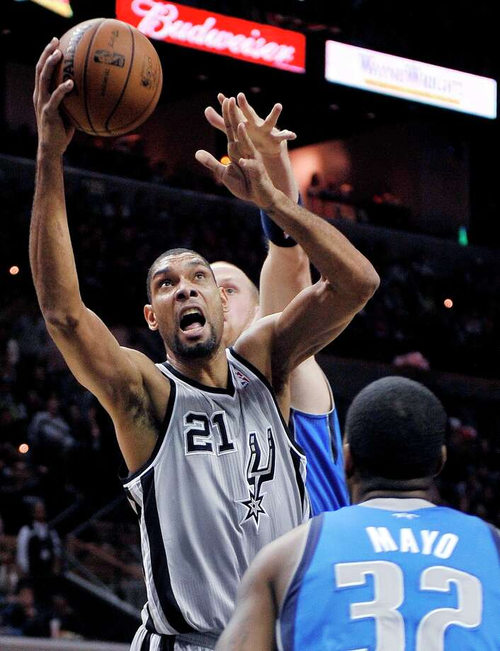 The Spurs' Tim Duncan (21) shoots between the Mavericks' O.J. Mayo (32) and Chris Kaman during the first half, Sunday, Dec. 23, 2012, in San Antonio. Photo: Darren Abate, Associated Press / FR115 AP