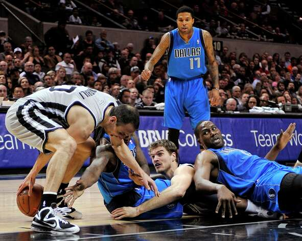 The Spurs' Manu Ginobili (left) and Tiago Splitter (center right) scrap for a loose ball against the Mavericks' Elton Brand (right) and Jae Crowder as Mavericks' Chris Douglas-Roberts (rear) watches during the first half, Sunday, Dec. 23, 2012, in San Antonio. Photo: Darren Abate, Associated Press / FR115 AP