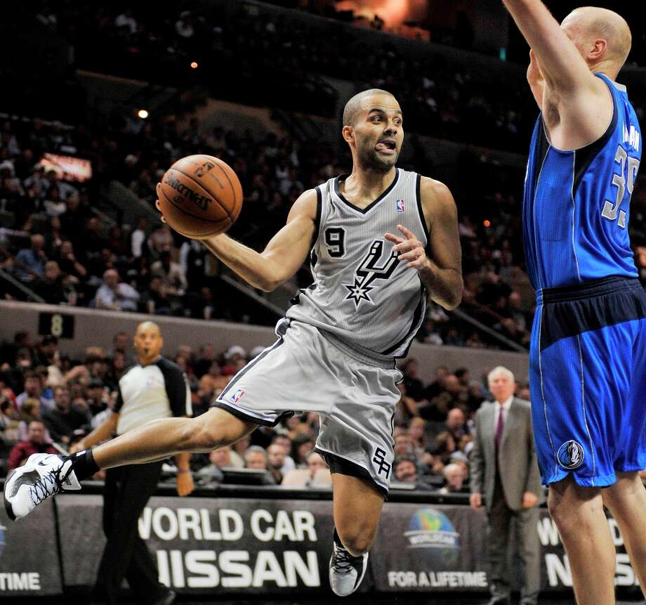 The Spurs' Tony Parker (left) passes around the Mavericks' Chris Kaman during the first half, Sunday, Dec. 23, 2012, in San Antonio. Photo: Darren Abate, Associated Press / FR115 AP