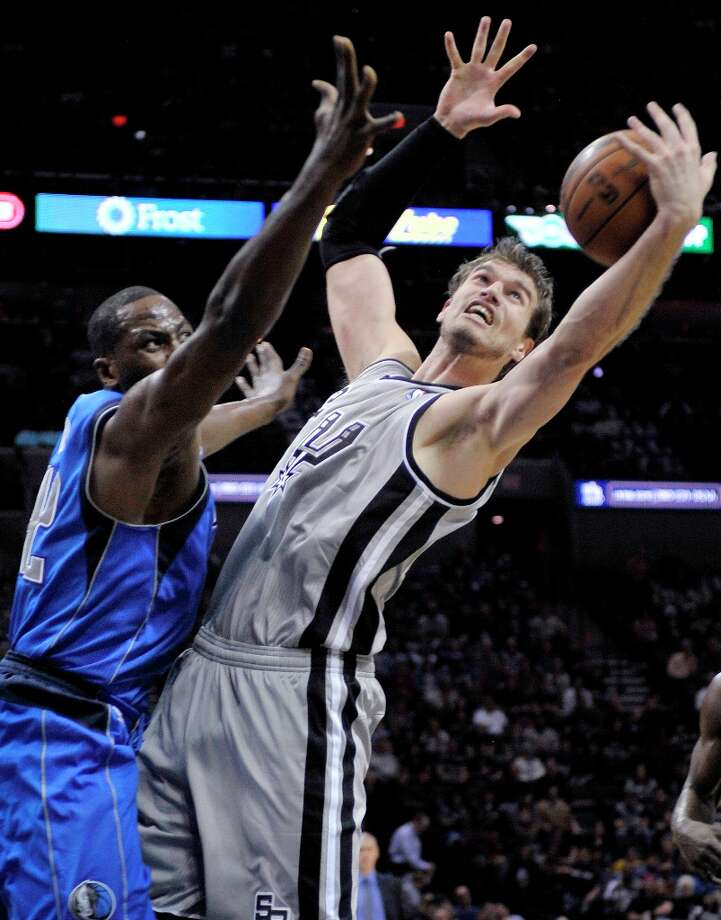 The Spurs' Tiago Splitter (right) falls as he is blocked by the Mavericks' Elton Brand during the first half, Sunday, Dec. 23, 2012, in San Antonio. Photo: Darren Abate, Associated Press / FR115 AP