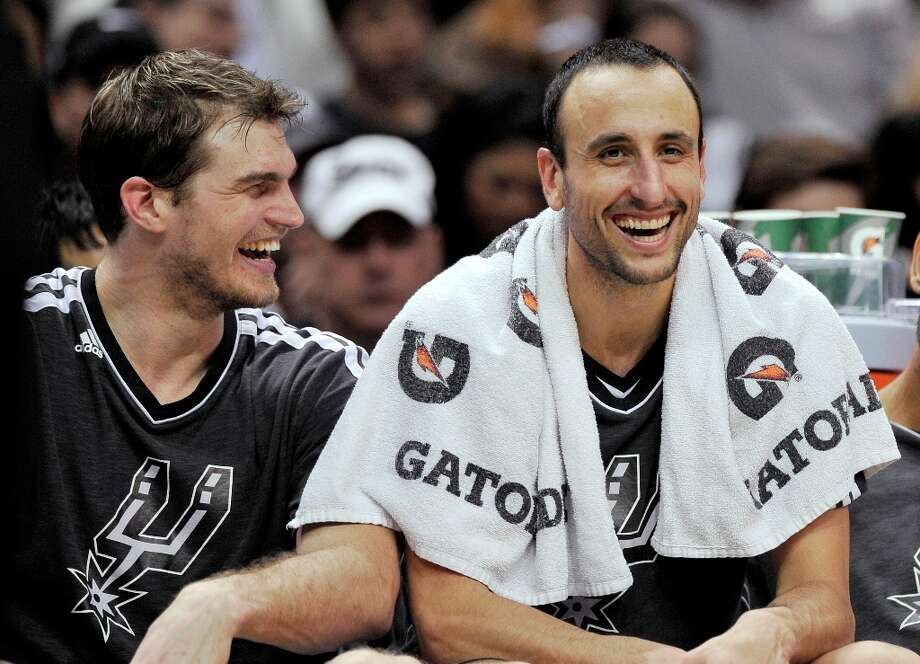 The Spurs' Manu Ginobili (right) laughs with Tiago Splitter during the second half against the Mavericks, Sunday, Dec. 23, 2012, in San Antonio. San Antonio won 129-91. Photo: Darren Abate, Associated Press / FR115 AP