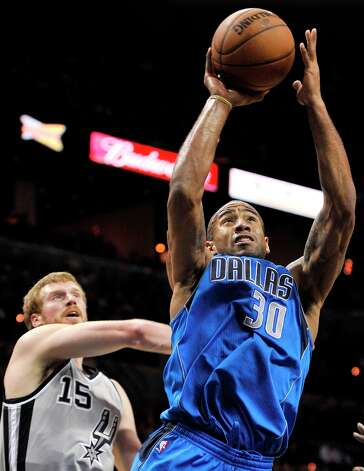 The Mavericks' Dahntay Jones (30) shoots ahead of the Spurs' Matt Bonner during the second half, Sunday, Dec. 23, 2012, in San Antonio. San Antonio won 129-91. Photo: Darren Abate, Associated Press / FR115 AP