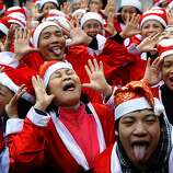 Members of a local Smiling Yoga club wearing Santa Claus costumes perform at a public park in Hanoi on December 23, 2012. Churches, shops, restaurants and shopping mails are decorated in the Southeast Asian nation with some six million catholics preparing to celebrate Christmas.  TOPSHOTS AFP PHOTO / HOANG DINH NamHOANG DINH NAM/AFP/Getty Images
