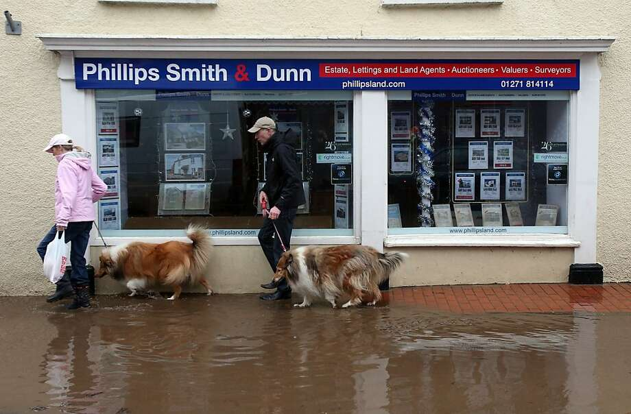 BARNSTAPLE, ENGLAND - DECEMBER 23:  A couple walking their dogs passes receding flood water in the centre of the Devonshire town of Braunton that was flooded yesterday on December 23, 2012 near Barnstaple, England. Flooding has brought further disruption to many parts of the UK including the South West of England that was particularly badly hit.  The Met Office are warning of further bands of heavy rain tonight and the Environment Agency has issued 100s of flood warnings for England including one severe warning for Cornwall.  (Photo by Matt Cardy/Getty Images) Photo: Matt Cardy, Getty Images