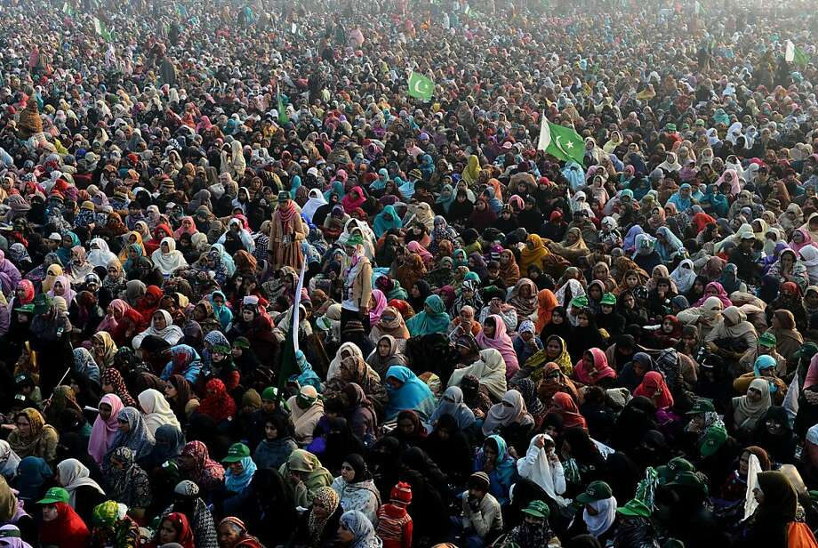 Pakistani supporters of Tehreek-e-Minhajul Quran or movement to follow the path of Koran listen to the religious leader Tahir ul Qadri in the public meeting in Lahore on December 23, 2012. An influential religious leader addressing a massive crowd of some 100,000 people gave the incumbent Pakistan government three weeks to launch electoral reforms or face a long march on Islamabad.  Arif Ali/AFP/Getty Images Photo: Arif Ali, AFP/Getty Images
