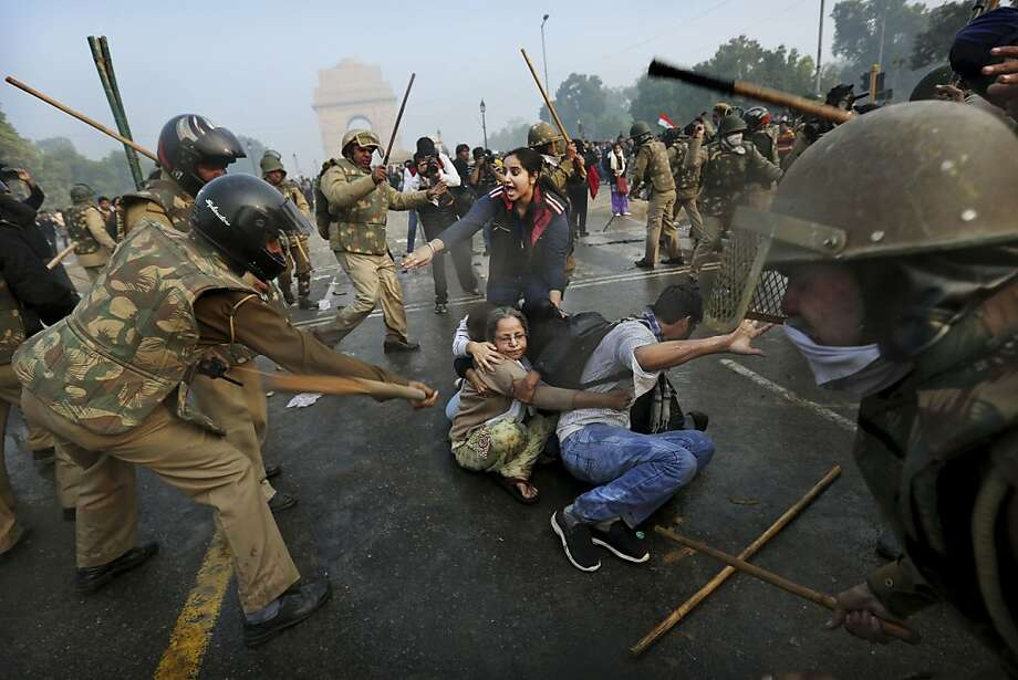 Protesters shield themselves as Indian police beat them with sticks during a violent demonstration near the India Gate against a gang rape and brutal beating of a 23-year-old student on a bus last week, in New Delhi, India, Sunday, Dec. 23, 2012. The attack last Sunday has sparked days of protests across the country. (AP Photo/Kevin Frayer) Photo: Kevin Frayer, Associated Press