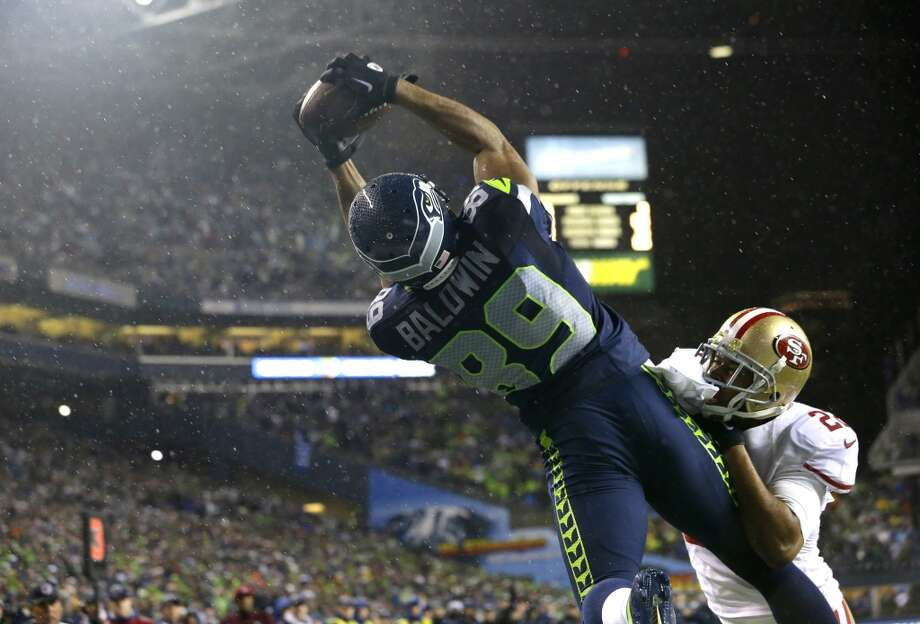 Seattle Seahawks' Doug Baldwin (89) comes down with a touchdown catch past the defense of San Francisco 49ers' Carlos Rogers (22) in the second half of an NFL football game, Sunday, Dec. 23, 2012, in Seattle.  (Elaine Thompson / Associated Press)