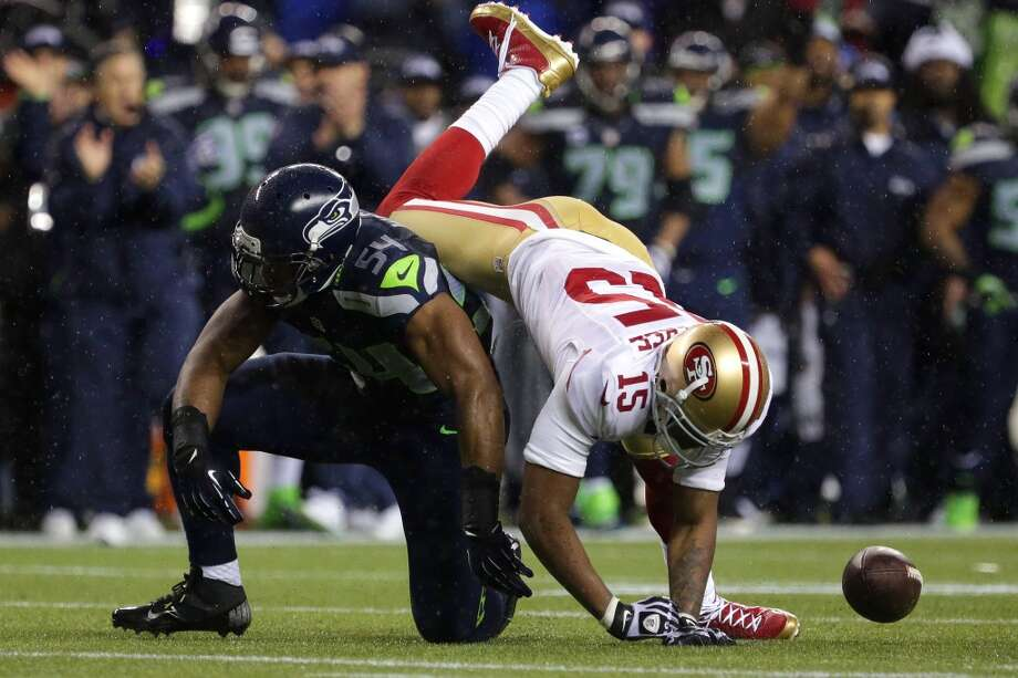 Michael Crabtree, right, of the San Francisco 49ers, tumbles over Seahawk Bobby Wagner, left, during the first half of a game Sunday, Dec. 23, 2012, at CenturyLink Field in Seattle, WA.  (Jordan Stead / Special to the Chronicle)