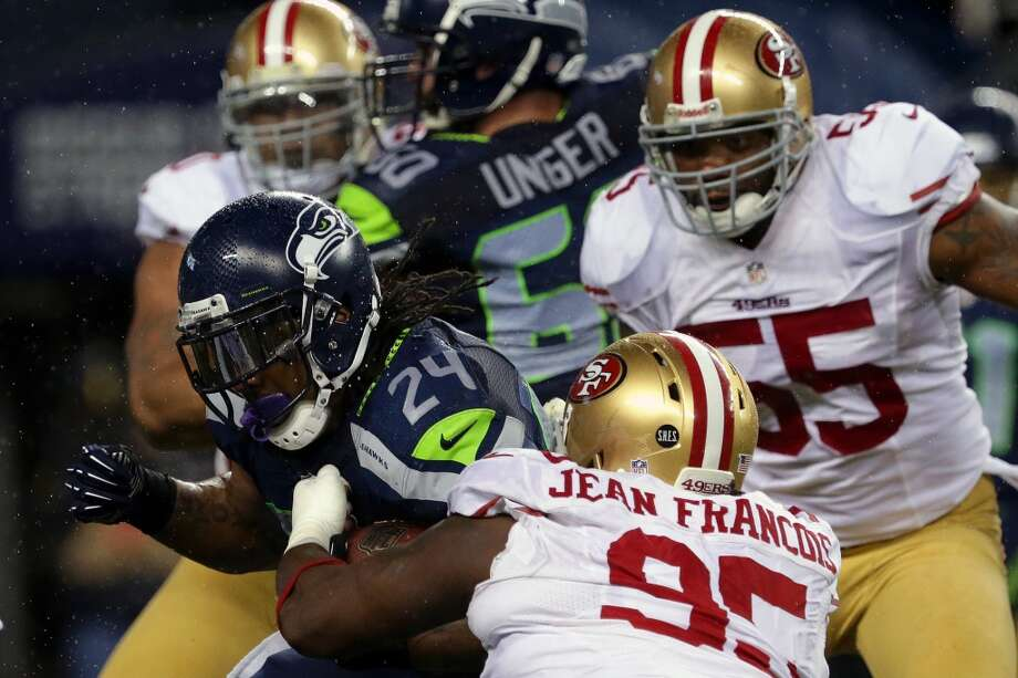 Marshawn Lynch, left, of the Seattle Seahawks, pushes through 49er defense during the first half of a game Sunday, Dec. 23, 2012, at CenturyLink Field in Seattle, WA.  (Jordan Stead / Special to the Chronicle)