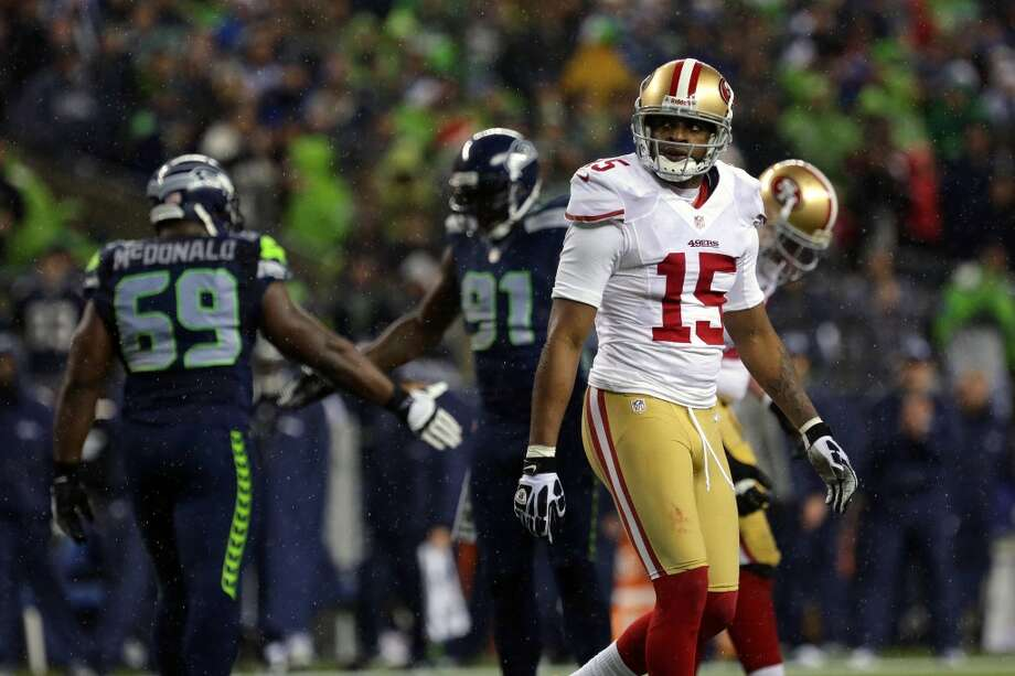 Michael Crabtree, right, of the San Francisco 49ers, glances at the scoreboard after a touchdown for the Seahawks during the first half of a game Sunday, Dec. 23, 2012, at CenturyLink Field in Seattle, WA.  (Jordan Stead / Special to the Chronicle)
