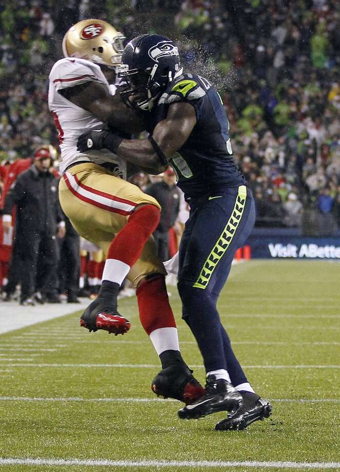 San Francisco 49ers' Vernon Davis, left, is hit by Seattle Seahawks' Kam Chancellor, right during a reception attempt in the first half of an NFL football game, Sunday, Dec. 23, 2012, in Seattle. (John Froschauer / Associated Press)