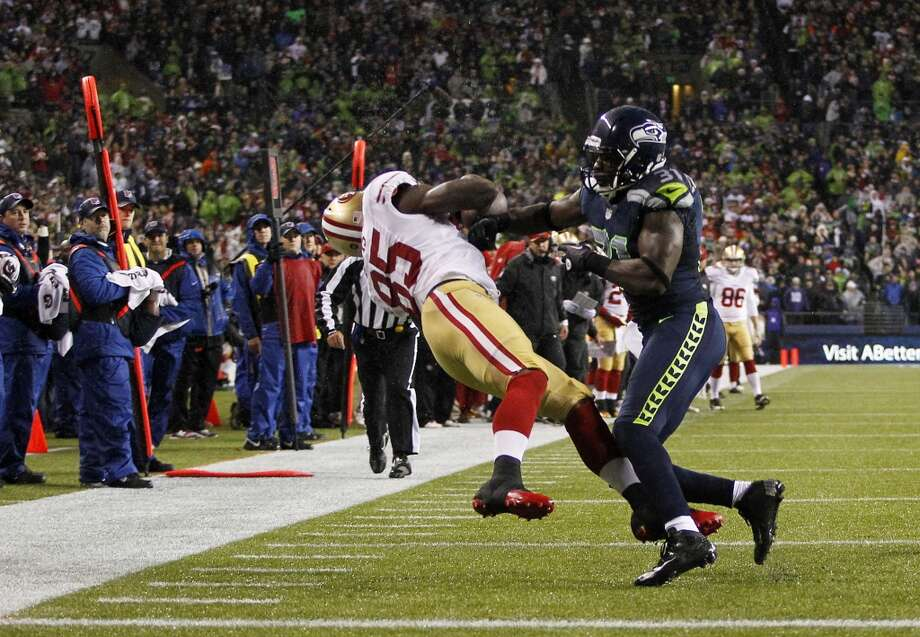 San Francisco 49ers' Vernon Davis, left, is hit by Seattle Seahawks' Kam Chancellor, right, during a reception attempt in the first half of an NFL football game, Sunday, Dec. 23, 2012, in Seattle.  (John Froschauer / Associated Press)