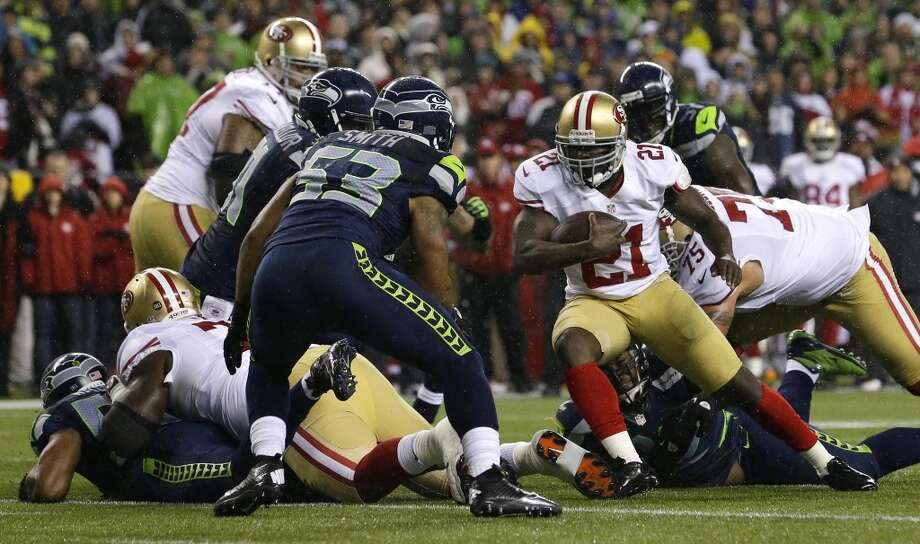 San Francisco 49ers' Frank Gore (21) rushes against Seattle Seahawks' Malcolm Smith (53) in the first half of an NFL football game, Sunday, Dec. 23, 2012, in Seattle.  (Elaine Thompson / Associated Press)