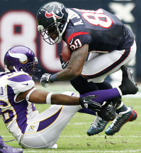 Vikings cornerback Antoine Winfield uses his hands and feet to trip up Texans receiver Andre Johnson, who caught seven passes for 97 yards. Photo: Brett Coomer, Staff / © 2012  Houston Chronicle