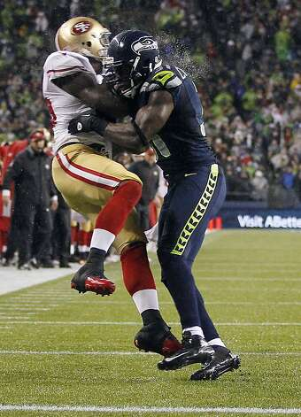 San Francisco 49ers' Vernon Davis, left, is hit by Seattle Seahawks' Kam Chancellor, right during a reception attempt in the first half of an NFL football game, Sunday, Dec. 23, 2012, in Seattle. (AP Photo/John Froschauer) Photo: John Froschauer, Associated Press