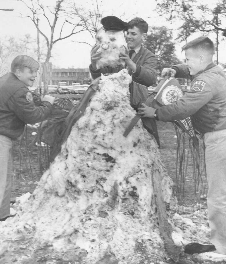 Philip Leggett, 12, Ritchie Harte, 14, and Bill Scott, 12, all students at San Antonio Academy, build a snowman for later snowball target practice after a storm hit the city on Feb. 22, 1966. Photo: San Antonio Express-News File Photo