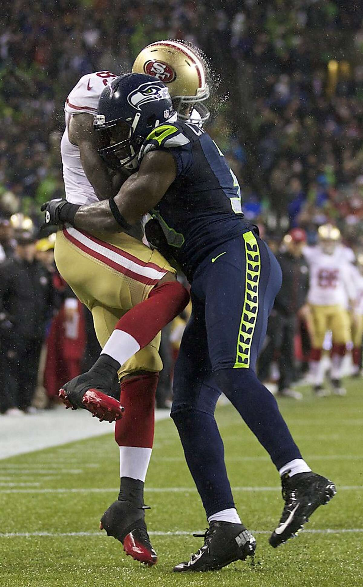 SEATTLE, WA - DECEMBER 23: Kam Chancellor #31 of the Seattle Seahawks hits Vernon Davis #85 of the San Francisco 49ers during a game at CenturyLink Field on December 23, 2012 in Seattle, Washington. (Photo by Stephen Brashear/Getty Images)