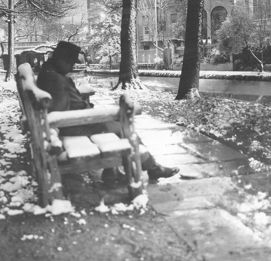 A man sits on a bench lining the snowy River Walk after a storm hit the city on Feb. 22, 1966. Photo: San Antonio Express-News File Photo