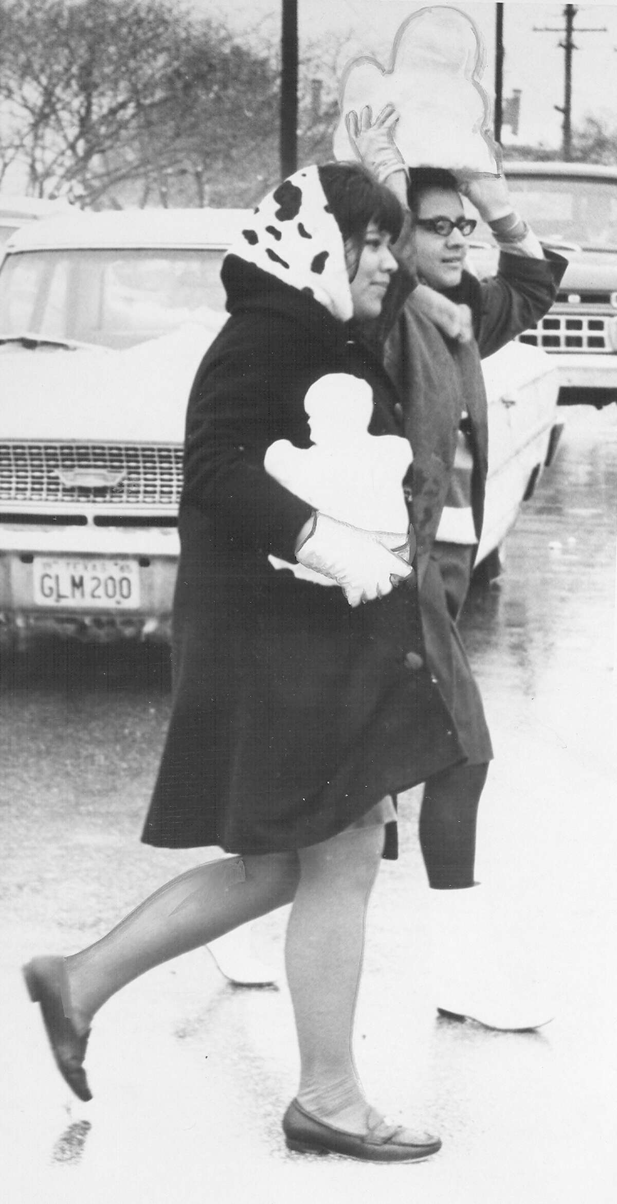 Two women carry small snowmen after a snow storm in San Antonio on Feb. 22, 1966.