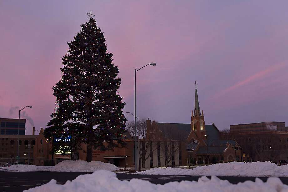A 60-foot-tall evergreen stands on Minnesota Avenue in  Sioux Falls, S.D., on Dec. 23, 2012. The tree started being decorated as a gift from Donald Weir to his wife, Dorothy, in 1992. Now that both Weirs have died, a local church keeps the tree lit each season to ensure the tradition continues. (AP Photo, Amber Hunt) Photo: Amber Hunt, Associated Press