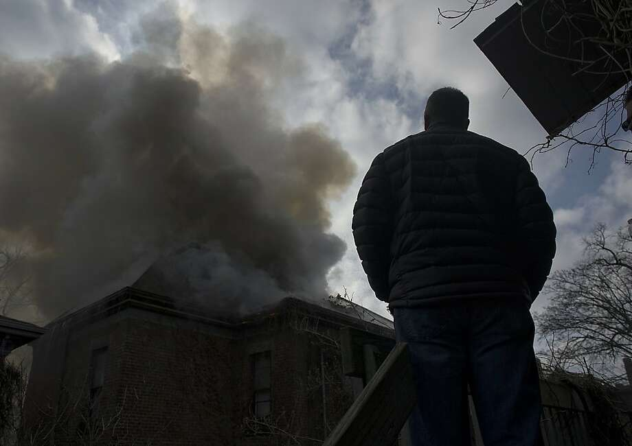 A bystander watches from a neighboring porch as the rear of the five apartment house at 1122 West Wayne Street burns Sunday morning, Dec. 23, 2012 in Fort Wayne, Ind. (AP Photo/The Journal Gazette, Swikar Patel) Photo: Renee C. Byer, Associated Press