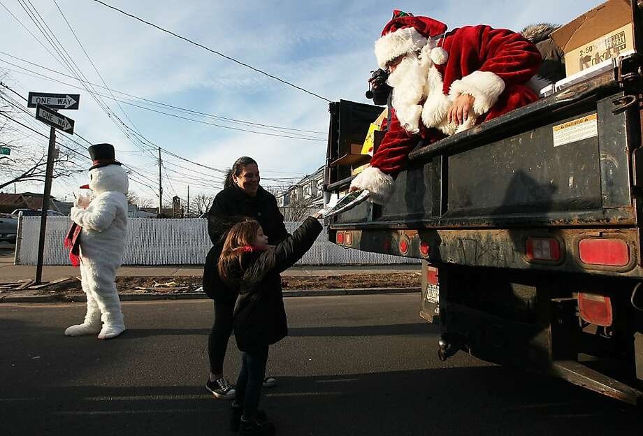 NEW YORK, NY - DECEMBER 23: Mike 'Loco' Hoffman, aka Santa Claus, passes out free gifts from the back of a truck to Gloria Lullo and her granddaughter Jolee in the Midland Beach neighborhood which was heavily damaged by Superstorm Sandy on December 23, 2012 in the Staten Island borough of New York City. Staten Island was hit hard by Sandy and some homes and businesses remain without power.  (Photo by Mario Tama/Getty Images) Photo: Mario Tama, Getty Images