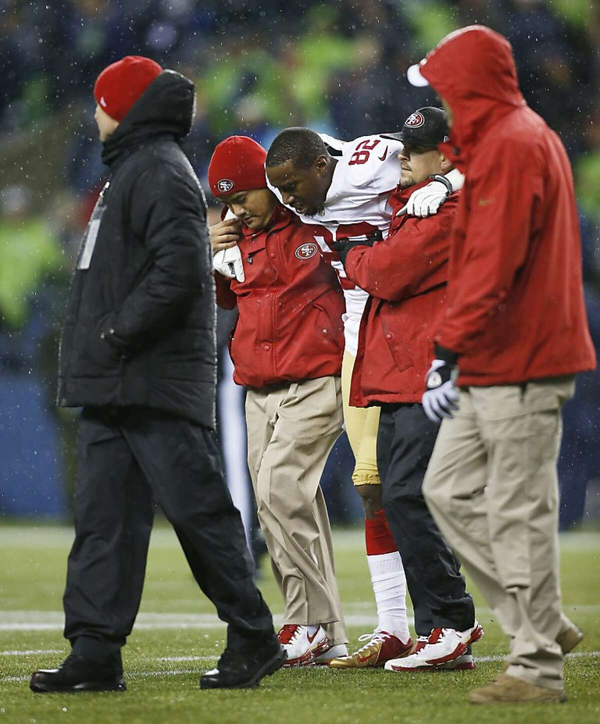 San Francisco 49ers Mario Manningham is helped off the field after an injury against the Seattle Seahawks in the second half of an NFL football game, Sunday, Dec. 23, 2012, in Seattle. (AP Photo/John Froschauer)
