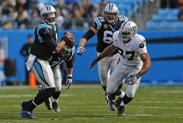 Carolina Panthers' Cam Newton (1) scrambles as Oakland Raiders' Andre Carter (97) pursues during the first half of an NFL football game in Charlotte, N.C., Sunday, Dec. 23, 2012. (AP Photo/Chuck Burton) Photo: Chuck Burton, Associated Press