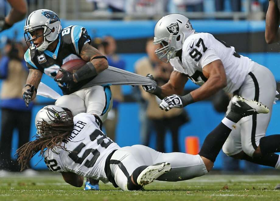 Oakland Raiders' Andre Carter (97) grabs the jersey of Carolina Panthers' Steve Smith (89) as Raiders' Philip Wheeler (52) reaches for Smith during the first half of an NFL football game in Charlotte, N.C., Sunday, Dec. 23, 2012. (AP Photo/Bob Leverone) Photo: Bob Leverone, Associated Press