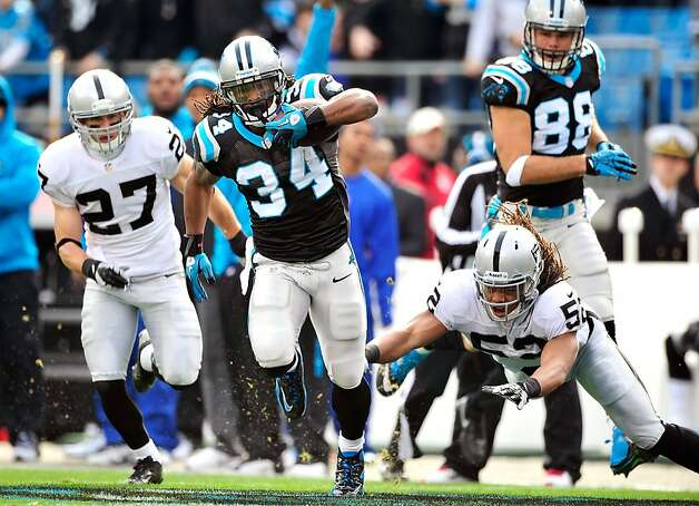 CHARLOTTE, NC - DECEMBER 23: DeAngelo Williams #34 of the Carolina Panthers breaks away from Philip Wheeler #52 of the Oakland Raiders during play at Bank of America Stadium on December 23, 2012 in Charlotte, North Carolina. (Photo by Grant Halverson/Getty Images) Photo: Grant Halverson, Getty Images