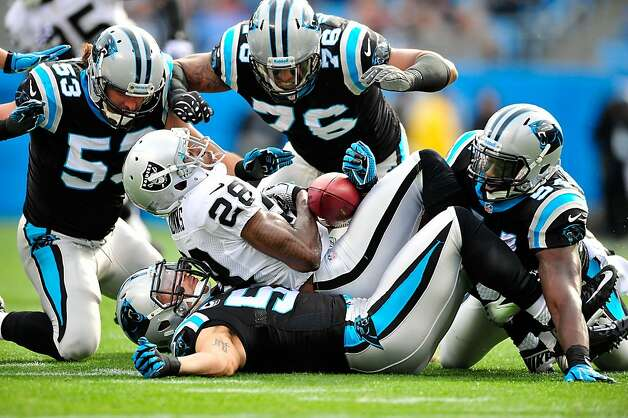 CHARLOTTE, NC - DECEMBER 23: Jason Phillips #53, Greg Hardy #76, Jason Williams #54 and Jordan Senn #57 of the Carolina Panthers tackle Phillip Adams #28 of the Oakland Raiders during play at Bank of America Stadium on December 23, 2012 in Charlotte, North Carolina. (Photo by Grant Halverson/Getty Images) Photo: Grant Halverson, Getty Images
