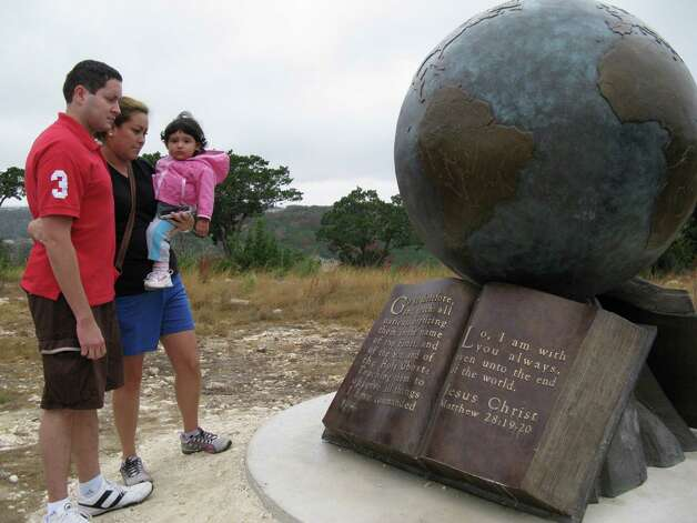 Luis Sosa (left) and his wife Yasmin, holding daughter Kaylee, admire one of the works displayed at the Coming King Sculpture Prayer Garden on a hill in Kerrville overlooking Interstate 10 on Dec. 3, 2012. Photo: Zeke MacCormack, San Antonio Express-News / San Antonio Express-News