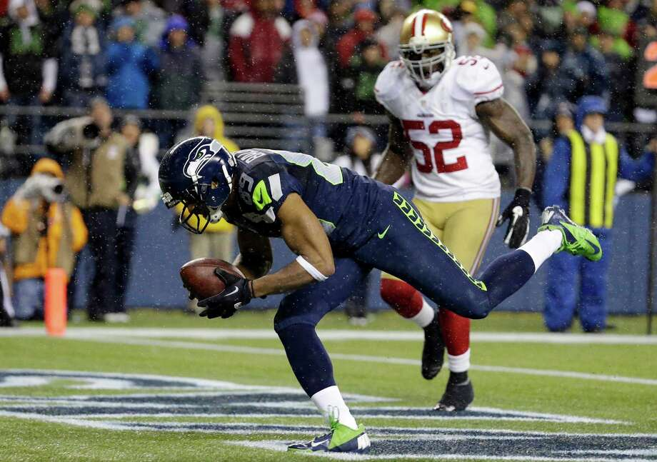 Seattle Seahawks' Doug Baldwin scores a touchdown as San Francisco 49ers' Patrick Willis (52) looks on in the second half of an NFL football game, Sunday, Dec. 23, 2012, in Seattle. Photo: AP