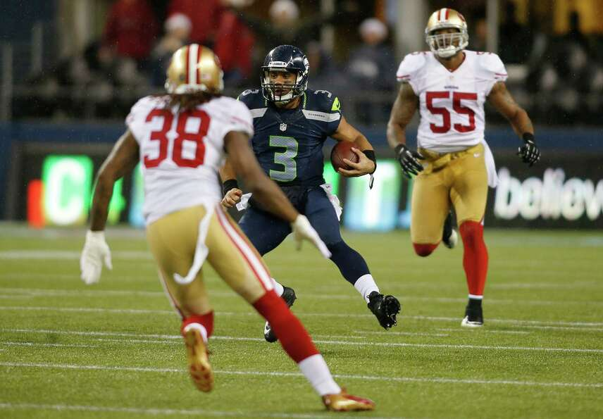 Seattle Seahawks quarterback Russell Wilson (3) looks for running room as he goes between San Franci