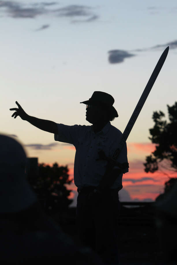 """Artist Max Greiner stands with his sword to start group activities at his newly installed sculpture """"The Empty Cross"""" at the Coming King Sculpture Prayer Garden in Kerrville in the evening on July 27, 2010. Photo: Tom Reel, San Antonio Express-News / © 2010 San Antonio Express-News"""