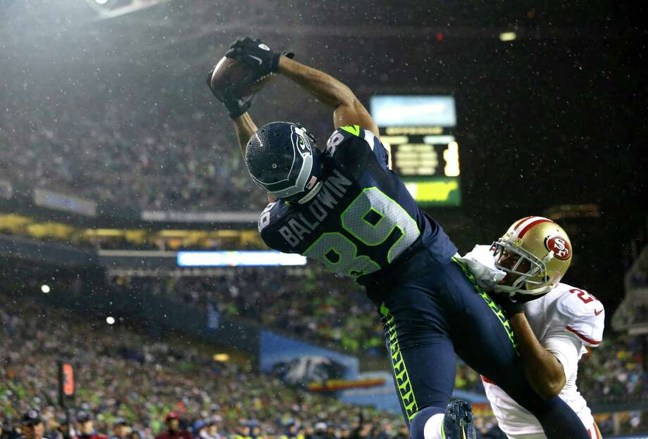 Seattle Seahawks' Doug Baldwin (89) comes down with a touchdown catch past the defense of San Francisco 49ers' Carlos Rogers (22) in the second half of an NFL football game, Sunday, Dec. 23, 2012, in Seattle. Photo: AP