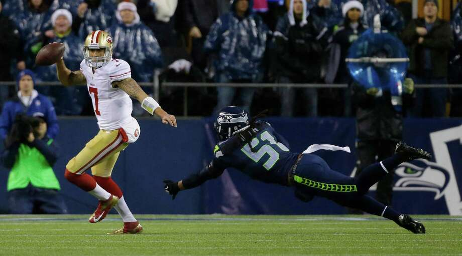 Seattle Seahawks Bruce Irvin (51) dives as he attempts to tackle San Francisco 49ers quarterback Colin Kaepernick (7) in the first half of an NFL football game, Sunday, Dec. 23, 2012, in Seattle. Photo: AP