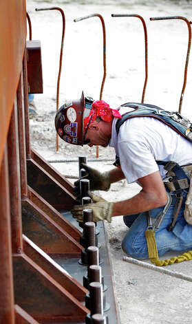 "A worker bolts down ""The Empty Cross"" after the Coming King Foundation project was raised at Interstate 10 and Texas 16 in Kerrville on July 27, 2010. Photo: Bob Owen, San Antonio Express-News / SAN ANTONIO EXPRESS-NEWS"