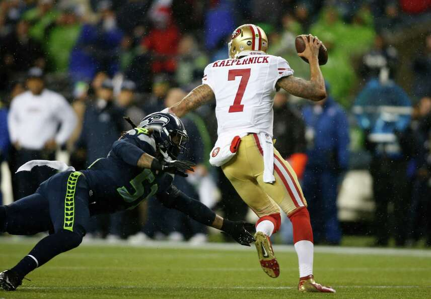 Seattle Seahawks' Bruce Irvin (51) tackles San Francisco 49ers quarterback Colin Kaepernick (7) in t
