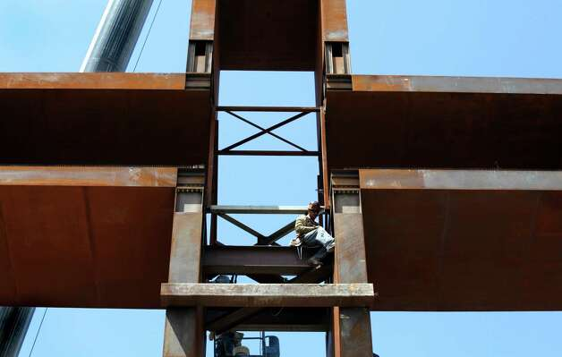 "A worker bolts the top portion to the base, as ""The Empty Cross"" is raised. The Coming King Foundation's project is at Interstate 10 and Texas 16 in Kerrville on July 27, 2010. Photo: Bob Owen, San Antonio Express-News / SAN ANTONIO EXPRESS-NEWS"