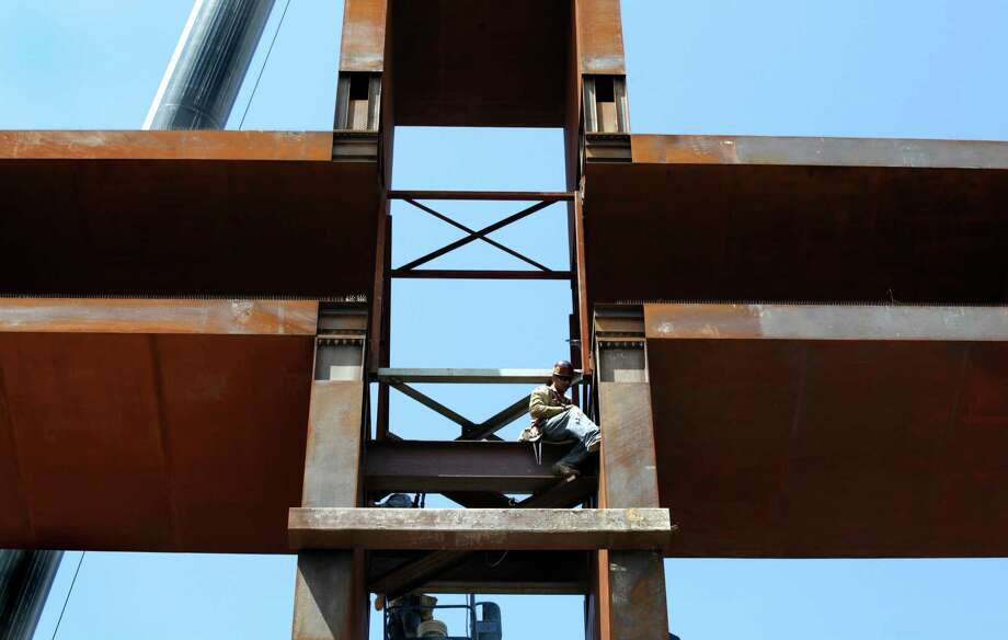"""A worker bolts the top portion to the base, as """"The Empty Cross"""" is raised. The Coming King Foundation's project is at Interstate 10 and Texas 16 in Kerrville on July 27, 2010. Photo: Bob Owen, San Antonio Express-News / SAN ANTONIO EXPRESS-NEWS"""