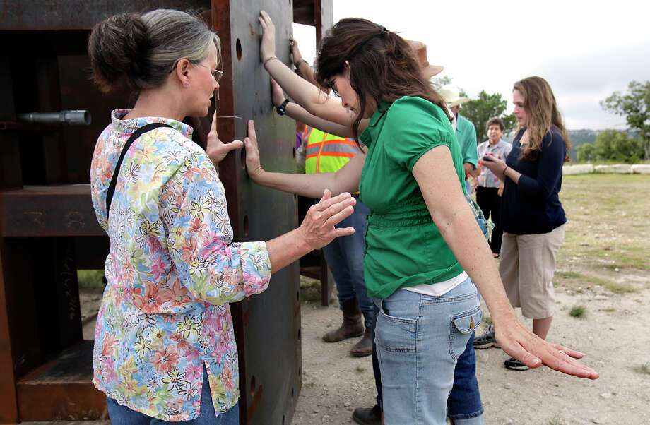"Worshipers Peggy Authement (left) and Becky Choat pray with others for ""The Empty Cross"" before it is raised to its base. The project is sponsored by the Coming King Foundation at Interstate 10 and Texas 16 in Kerrville on July 27, 2010. Photo: Bob Owen, San Antonio Express-News / SAN ANTONIO EXPRESS-NEWS"