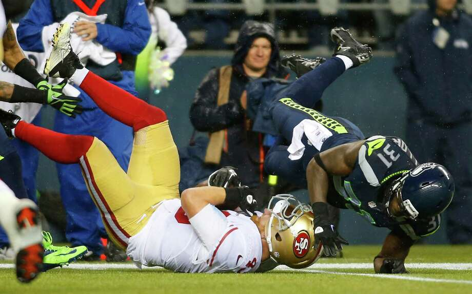 San Francisco 49ers' Bruce Miller (49) goes down from a hard hit by Seattle Seahawks' Kam Chancellor (31) in the first half of an NFL football game, Sunday, Dec. 23, 2012, in Seattle. Photo: AP