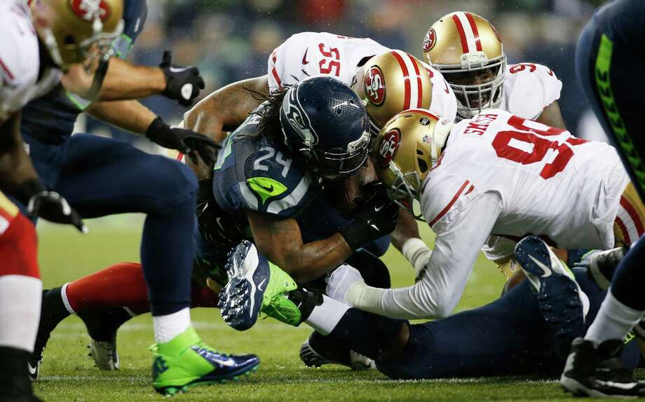 Seattle Seahawks Marshawn Lynch is tackled by San Francisco 49ers Aldon Smith (99) and Ahmad Brooks (55) in the first half of an NFL football game, Sunday, Dec. 23, 2012, in Seattle. Photo: AP