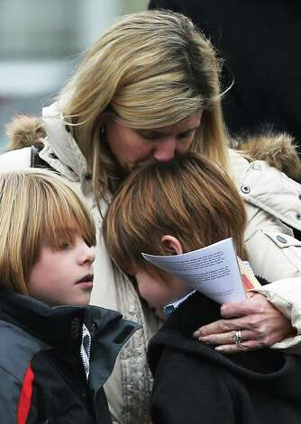 NEWTOWN, CT - DECEMBER 17:  A woman comforts a boy as mourners depart Honan Funeral Home after the funeral for six-year-old Jack Pinto on December 17, 2012 in Newtown Connecticut. Pinto was one of the 20 students killed in the Sandy Hook Elementary School mass shooting. Photo: Mario Tama / 2012 Getty Images