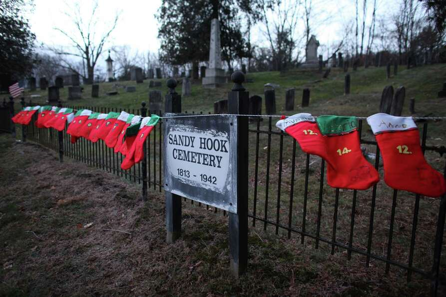Twenty-six Christmas stockings hang on the fence at the Sandy Hook Cemetery across from the entrance