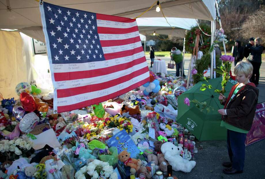 Anders Mueller 8, places roses at a growing memorial near the entrance to Sandy Hook Elementary School. Photo: JOSHUA TRUJILLO / HEARST NEWSPAPERS