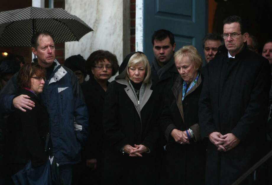 Connecticut Governor Dannel Malloy, right, and First Selectman Patricia Llodra, second from right, lead a moment of silence as a bell tolls 26 times in front of Edmond Town Hall in Newtown. The moment of silence and bell tolling was held across the U.S. on Friday, December 21, 2012, the one week anniversary of the Sandy Hook shootings. Photo: JOSHUA TRUJILLO / HEARST NEWSPAPERS