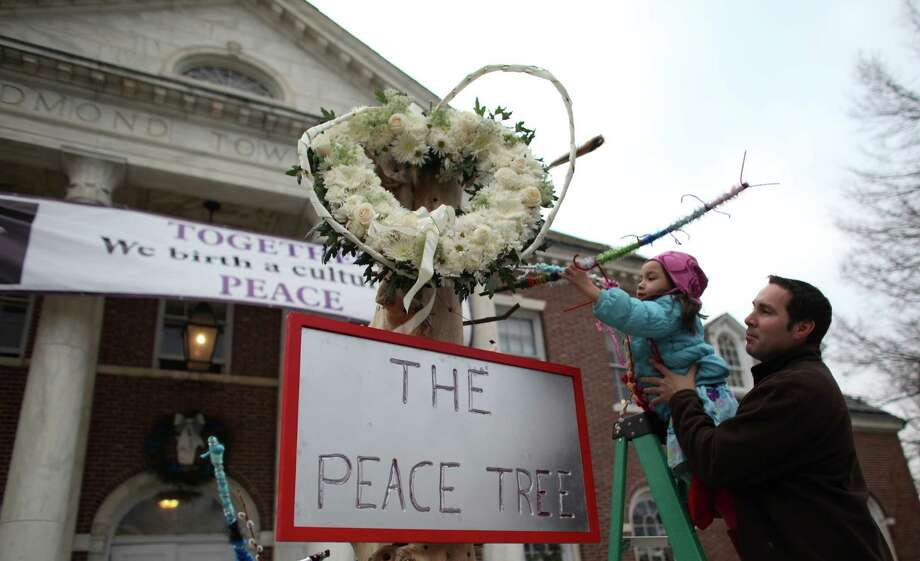 "Eric Malon and his daughter Alexis, 5, attach branches to ""The Peace Tree"" in front Edmond Town Hall in Newtown. Photo: JOSHUA TRUJILLO / HEARST NEWSPAPERS"