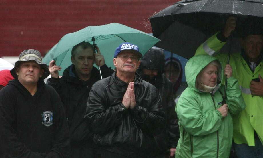 """People, including Joe Saleem, center, observe a moment of silence led by Connecticut Governor Dannel Malloy, Lt. Governor Nancy Wyman and First Selectman Patricia Llodra in front of Edmond Town Hall in Newtown. The moment of silence and bell tolling was held across the U.S. on Friday, December 21, 2012, the one week anniversary of the Sandy Hook shootings. Saleem said he lived in Newtown for 54 years but moved to North Carolina. But after the violence that took 28 people, Saleem returned to his hometown. """"I've had three sleepless nights,"""" he said. Photo: JOSHUA TRUJILLO / HEARST NEWSPAPERS"""
